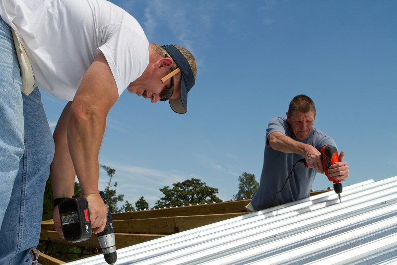 two workers installing a metal roof